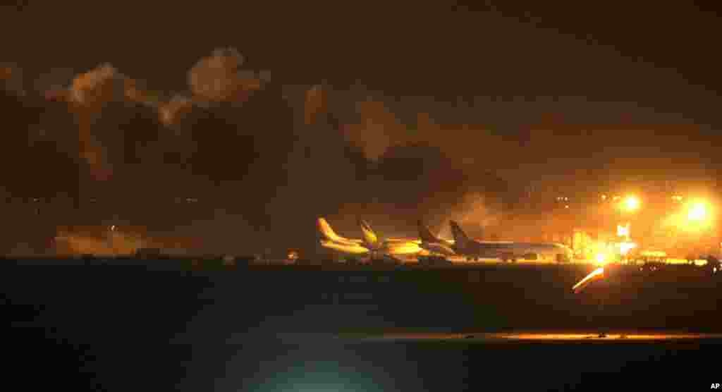 Fire illuminates the sky above the Jinnah International Airport in Karachi, Pakistan, June 8, 2014. Gunmen disguised as police guards attacked a terminal with machine guns and a rocket launcher during a five-hour siege that killed 28 people as explosions echoed into the night, while security forces retaliated and killed all the attackers, officials said.