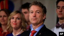 FILE - Republican presidential candidate, Sen. Rand Paul, R-Ky, stands with his wife, Kelley, as he waits to speaks to supporters during a caucus night party at the Scottish Rite Consistory in Des Moines, Iowa, Feb. 1, 2016.