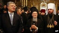 El Patriarca Ecuménico Bartolomé, centro, junto al presidente de Ucrania, Petro Poroshenko, izquierda, y Epifaniy, el jefe de la Iglesia Ucraniana Metropolitana.