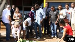 People lay flowers and pay their respects where constitutional law expert Gilles Cistac was murdered on March 3, 2015 in Maputo, Mozambique.