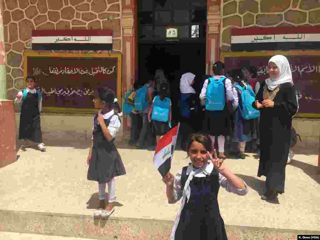 An Iraqi student holds Iraq's flag in one hand and does the V sign with her other hand, Belqis Elementary School (right side of Mosul), July 18, 2017.