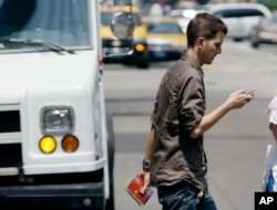 FILE - A man crosses a street in downtown Chicago while checking his phone.