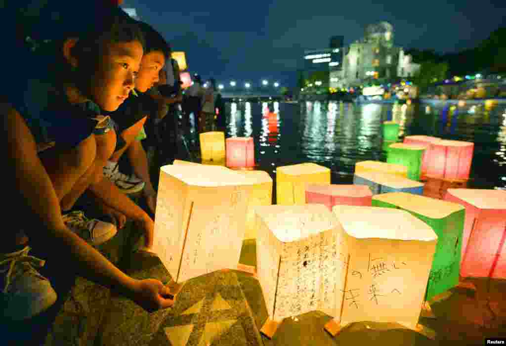 People release paper lanterns on the Motoyasu River in remembrance of victims on the 69th anniversary of the bombing of Hiroshima, Japan.