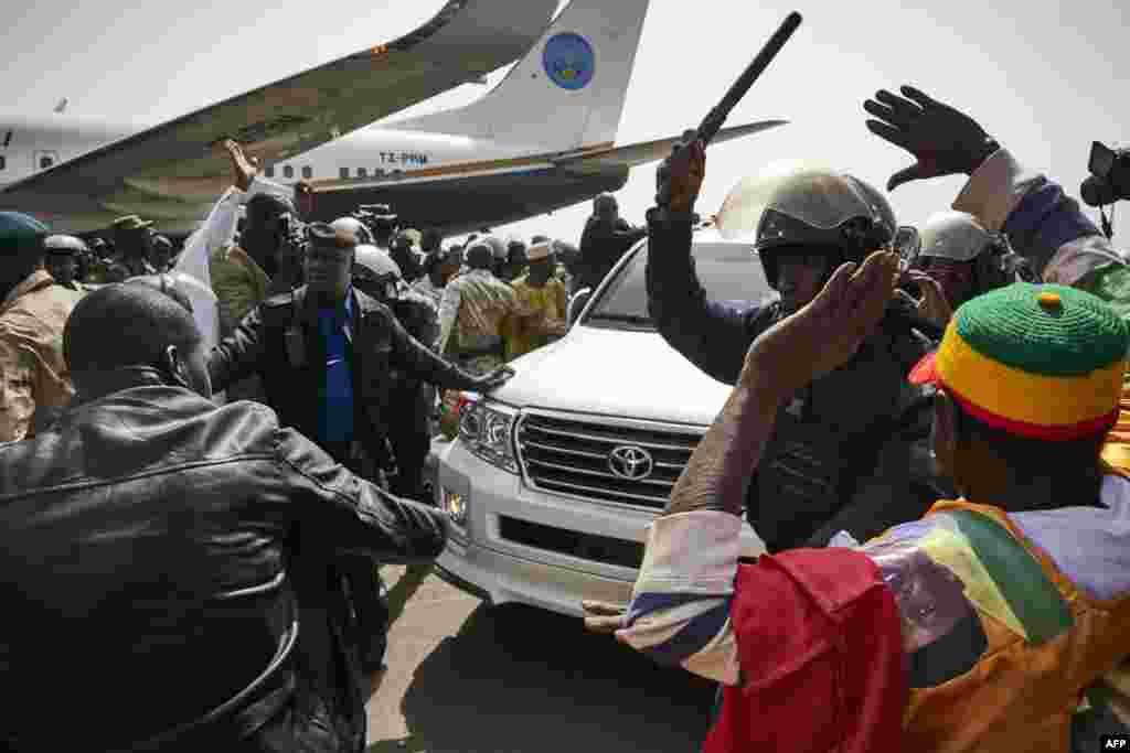 La police repoussant la foule lors du retour au Mali de l'ancien président Amadou Toumani Touré à l'aéroport de Bamako, le 24 décembre 2017.