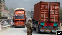 FILE - U.S. soldier watches trucks crossing Torkham gate border between Afghanistan and Pakistan in Nangarhar province, Afghanistan.