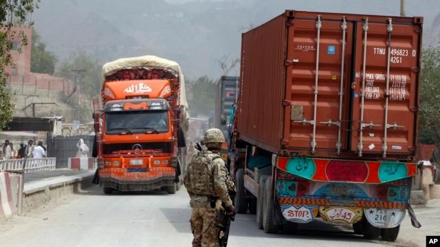 U.S. soldier watches trucks crossing Torkham gate border between Afghanistan and Pakistan in Nangarhar province, Afghanistan, July 21, 2011.