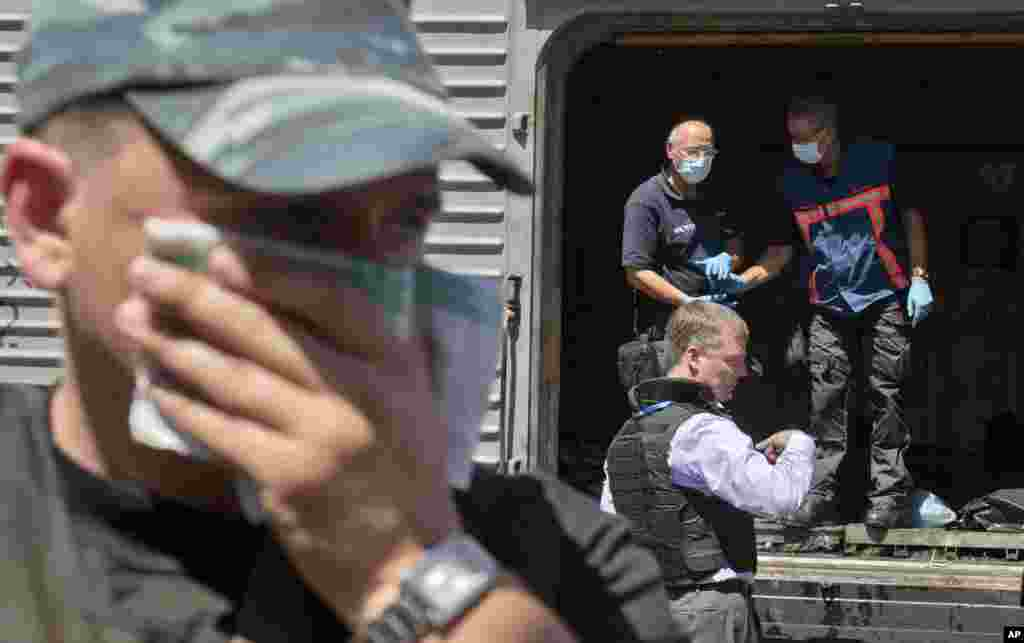 A man covers his face with a rag as deputy head of the OSCE mission to Ukraine Alexander Hug stands outside a refrigerated train as members of Netherlands' National Forensic Investigations Team inspect bodies, seen in plastic bags, Torez, eastern Ukraine, July 21, 2014.