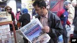 一男子读题为恐怖分子袭击阿梅纳斯绑架人质的报纸