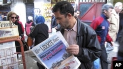 """A man reads a newspaper headlining """"Terrorist attack and kidnapping in In Amenas,"""" at a news stand in Algiers, January 17, 2013."""