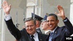 Presiden Barack Obama dan Presiden Polandia Bronislaw Komorowski melambaikan tangan ke arah kerumunan wartawan setibanya di Istana Presiden di Warsawa.