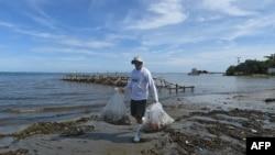 Israeli manager of Soda Stream, Daniel Birnbaum, collects plastic bottles at the beach of Roatan, Honduras, Oct. 9, 2018. The island off the Atlantic Coast of Honduras is a tourist destination.