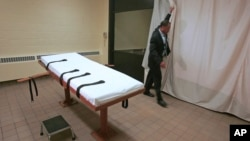 FILE – Larry Greene, public information director of the Southern Ohio Correctional Facility, demonstrates how a curtain is pulled between the death chamber and witness room at the prison in Lucasville, Ohio, in 2005. Ohio plans to resume executions in January 2017.