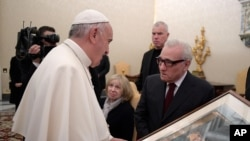 """Pope Francis looks at a painting given to him as a gift from director Martin Scorsese, right, on the occasion of their private audience at the Vatican, Nov. 30, 2016. Francis has met with Scorsese, whose new film, """"Silence,"""" about Jesuit missionaries in 17th-century Japan, was screened this week in Rome."""