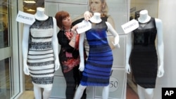 Shop manager Debbie Armstrong adjusts a two tone dress in a window display of a shop in Lichfield, England, Friday Feb. .27, 2015.
