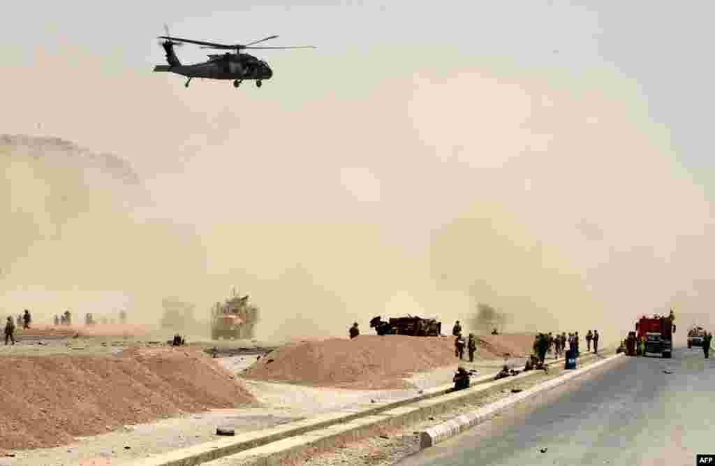 A U.S. black hawk helicopter flies over the site of a Taliban suicide attack in Kandahar, Afghanistan. A suicide bomber rammed a vehicle filled with explosives into a convoy of foreign forces in the country's restive southern province, causing casualties, officials said.