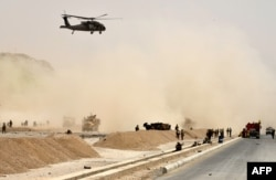 FILE - A U.S. black hawk helicopter flies over the site of a Taliban suicide attack in Kandahar, Afghanistan, Aug. 2, 2017.