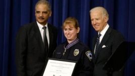 Vice President Joe Biden and Attorney General Eric Holder present the Medal of Valor to Officer Julie Olson of the Maplewood, Minnesota, Police Department, during a ceremony in the Eisenhower Executive Office Building on the White House complex in Washing