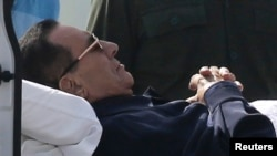 Cựu Tổng thống Ai Cập Hosni Mubarak nằm trên cáng trong khi được đưa đến toà án ở Cairo, 27/9/2014.