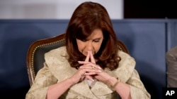 Argentine President Cristina Fernandez listens to a speech by Adelmo J.J.Gabbi, president of the Buenos Aires Stock Exchange (BCBA), during the ceremony for the 160th anniversary of the stock exchange in Buenos Aires, Argentina, Aug. 20, 2014.
