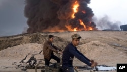 FILE - Young Iraqis ride bicycles next to a burning oil well in Qayyara, about 50 kilometers (30 miles) south of Mosul, Iraq, Oct. 23, 2016. The Islamic State group has launched diversionary attacks. Last week's assault on Kirkuk offers a glimpse at the kind of response it might mount as Iraqi forces close in on Mosul.