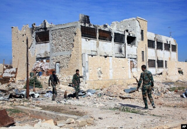 FILE - This Wednesday, Nov. 11, 2015, file photo released by the Syrian official news agency SANA, shows Syrian government troops walk inside the Kweiras air base, east of Aleppo, Syria.