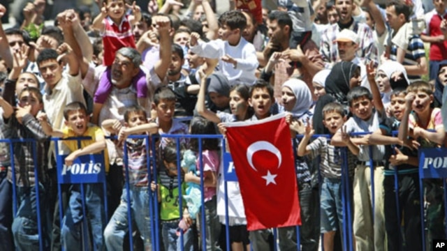 Syrian refugees shout slogans as they protest against Syrian President Bashar al-Assad at a refugee camp in the Turkish border town of Yayladagi in Hatay province, July 1, 2011