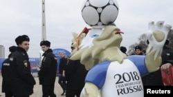 Police officers walk past the official mascot for the 2018 FIFA World Cup Russia, Zabivaka, during the opening of a soccer park in Rostov-on-Don, Russia, March 31, 2018
