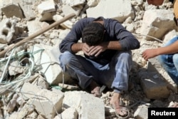 A man whose relatives were killed in an airstrike grieves amid rubble in the rebel-held al-Qaterji neighborhood of Aleppo, Syria, Oct. 11, 2016.