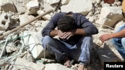 一名男子坐在遭俄羅斯轟炸的阿勒頗社區。