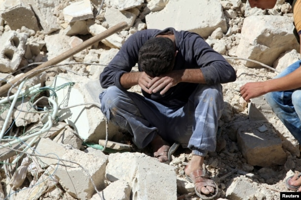 FILE - A man reacts on the rubble of damaged buildings after losing relatives to an airstrike in the besieged rebel-held al-Qaterji neighborhood of Aleppo, Syria, Oct. 11, 2016.