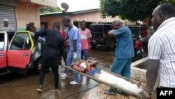 Quelques personnes transportent un blessé après une fusillade à Conakry, le 7 novembre 2018.