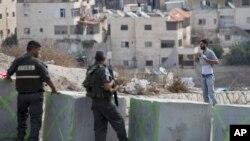 Un Palestinien soulève sa chemise devant des policiers qui patrouillent à la frontière israélienne dans le quartier d'Issawiyeh in Jérusalem, Oct. 20, 2015. (AP Photo/Ariel Schalit)