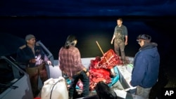 The Stevens family hunting crew reacts as a boat pulls into camp with a fresh moose kill after nightfall, September 15, 2021, near Stevens Village, Alaska.  The Yukon River becomes treacherous to navigate in one night.