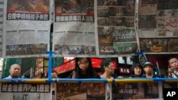Visitors view the latest newspaper coverage of clashes between protesters and police at a sit-in protest in Hong Kong, Sept. 29, 2014.