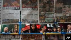 人们在香港阅读关于静坐示威民众和警察冲突的新闻报道(2014年9月29日)