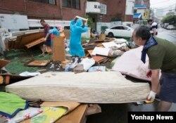 대한적십자사와 지방자치단체 관계자들이 24일 인천 부평구 인근 주거지 수해복구작업을 돕고 있다.