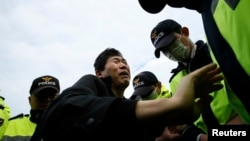 "A family member of a passenger missing after the South Korean ferry ""Sewol"" capsized is blocked by police during a protest in Jindo, demanding the search and rescue operation be sped up on April 20, 2014."