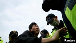"A family member of a passenger missing after the South Korean ferry ""Sewol"" capsized is blocked by police during a protest in Jindo calling for a meeting with President Park Geun-hye and demanding the search and rescue operation be speeded up, April 20, 2014."