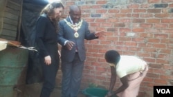 FILE: An official of the Bill and Melinda Gates Foundation and Harare mayor Bernard Manyenyeni talking to a local resident. (Photo: Irwin Chifera)