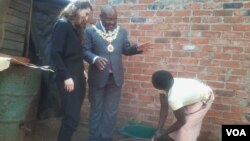An official of the Bill and Melinda Gates Foundation (left) and Harare mayor Bernard Manyenyeni talking to a local resident. (Photo: Irwin Chifera)