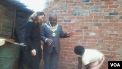 An official of the Bill and Melinda Gates Foundation and Harare mayor Bernard Manyenyeni talking to a local resident. (Photo: Irwin Chifera)