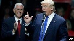 """ປະທານາທິບໍດີ ສະຫະລັດ ທີ່ໄດ້ຮັບເລືອກໃໝ່ ທ່ານ Donald Trump ກ່າວຖະແຫລງ ໃນຂະນະທີ່ຮອງປະທານາທິບໍດີ ທີ່ໄດ້ຮັບເລືອກໃໝ່ ທ່ານ Mike Pence ຜູ້ປົກຄອງລັດ Indiana ຢືນຢູ່ຄຽງຂ້າງ ໃນລະຫວ່າງການຊຸມນຸມ ໂຄສະນາຫາສຽງ, ວັນທີ 7 ພະຈິກ 2016, ໃນເມືອງ Manchester ລັດ New Hampshire, ຊຶ່ງໃນວັນພະຫັດມື້ນີ້ ທັງສອງທ່ານ ຈະໄປຢ້ຽມຢາມ ລັດ Indiana ແລະ ລັດ Ohio ໃນ """"ການເດີນທາງເພື່ອຂອບໃຈ."""""""