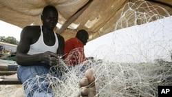 Des pêcheurs préparent leurs filets pour partir en mer au port de Guinée-Bissau, le 10 mars 2009.