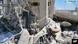 A Syrian man checks his destroyed house that was damaged by a Syrian forces air strike in the town of Qusair.