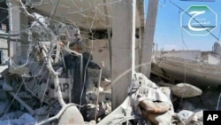 This citizen journalism image provided by Qusair Lens, which has been authenticated based on its contents and other AP reporting, shows a Syrian man checking his destroyed house that was damaged by a Syrian forces air strike in the town of Qusair, near th