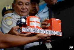 FILE - Head of Indonesian National Transportation Safety Committee Tatang Kurniadi, center, shows the cockpit voice recorder from AirAsia Flight 8501 during a press conference in Pangkalan Bun, Central Borneo, Indonesia.