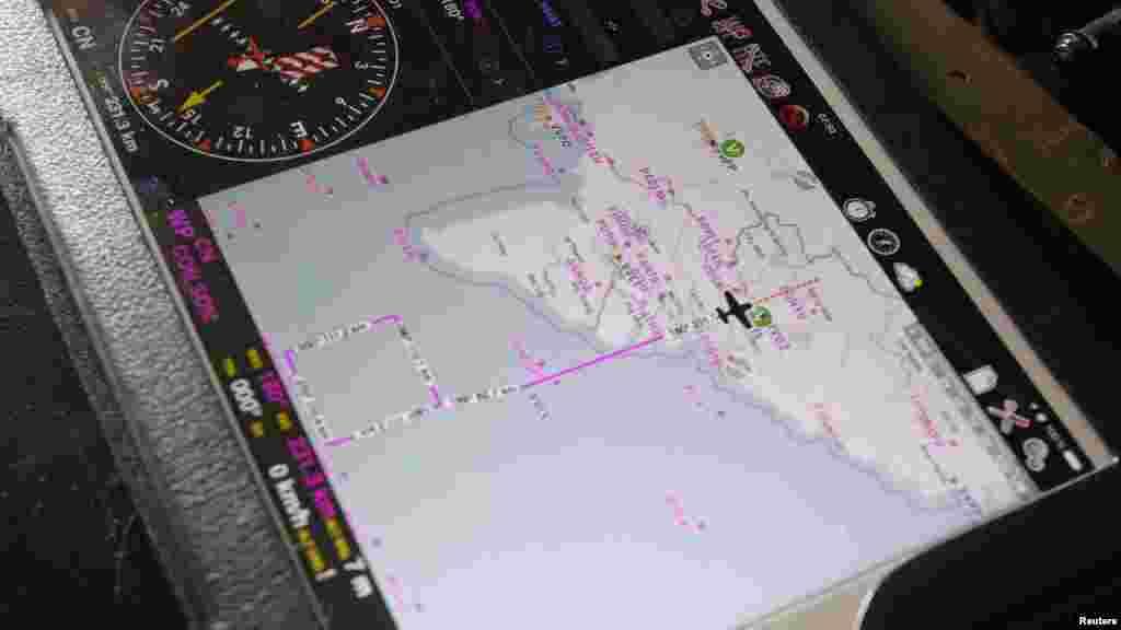 La zone de recherche est visible sur un iPad d'un officier militaire à bord d'un avion, 13 mars 2014.