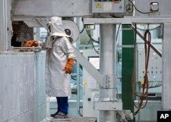 Seorang pekerja mengenakan APD, memeriksa proses produksi di pusat daur ulang dan pengecoran aluminium perusahaan AS Novelis Inc., yang berkantor pusat di Atlanta, AS, di Nachterstedt, Jerman tengah, Rabu, 1 Oktober 2014. (Foto: dok).