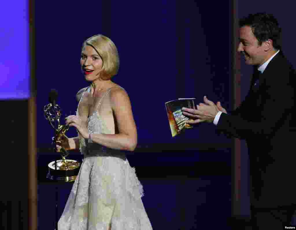 "Actress Claire Danes accepts the award for Outstanding Lead Actress In A Drama Series for her role in ""Homeland"" from presenter Jimmy Fallon at the 65th Primetime Emmy Awards in Los Angeles, Sept. 22, 2013."