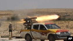 An anti-Gaddafi fighter fires a multiple-rocket launcher near Sirte, the hometown of deposed leader Moammar Gaddafi, September 17, 2011.